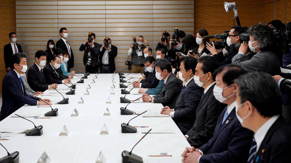 Премьер-министр Японии Синдзо Абэ (крайний слева) во время встречи по ситуации с коронавирусом