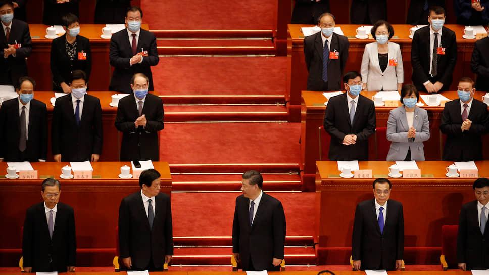 Высшему китайскому руководству (на переднем плане) во главе с председателем КНР Си Цзиньпином (в центре) и премьером Ли Кэцяном (второй справа) была оказана привилегия присутствовать на открытии сессии без масок