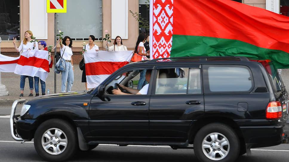На улицах Минска в пятницу развернулась «война флагов»: сторонники Александра Лукашенко ездили с красно-зелеными, оппозиционеры стояли в цепи с бело-красно-белыми