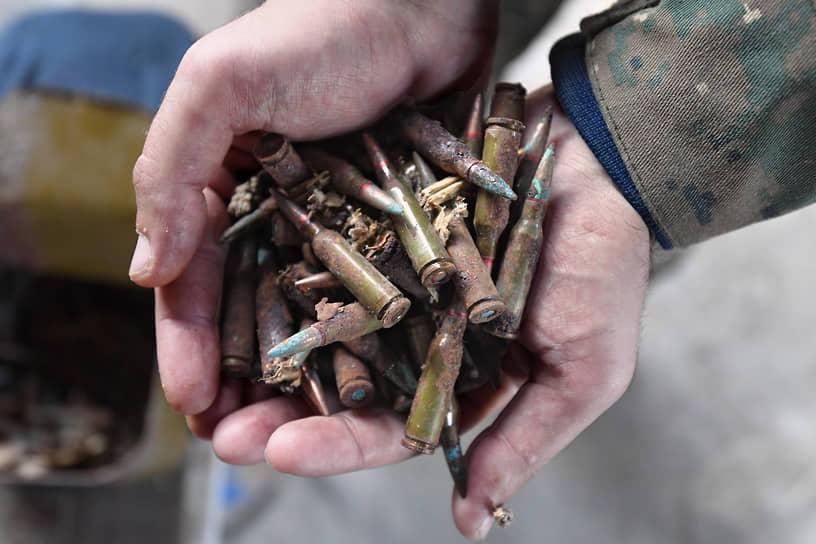 Местный житель демонстрирует собранные после обстрелов патроны