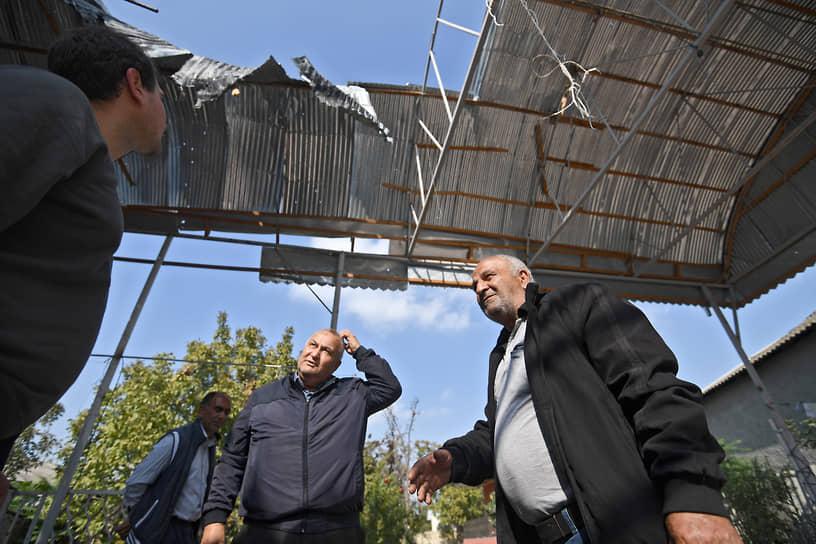 Жители Барды стоят под покореженной от обстрелов крышей