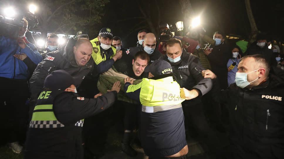 Полицейские задерживают мужчину во время митинга против результатов парламентских выборов в Грузии