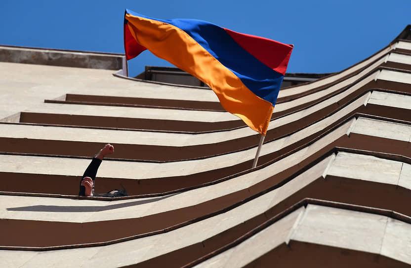 Жители города на балконе дома с государственным флагом Армении во время марша оппозиции
