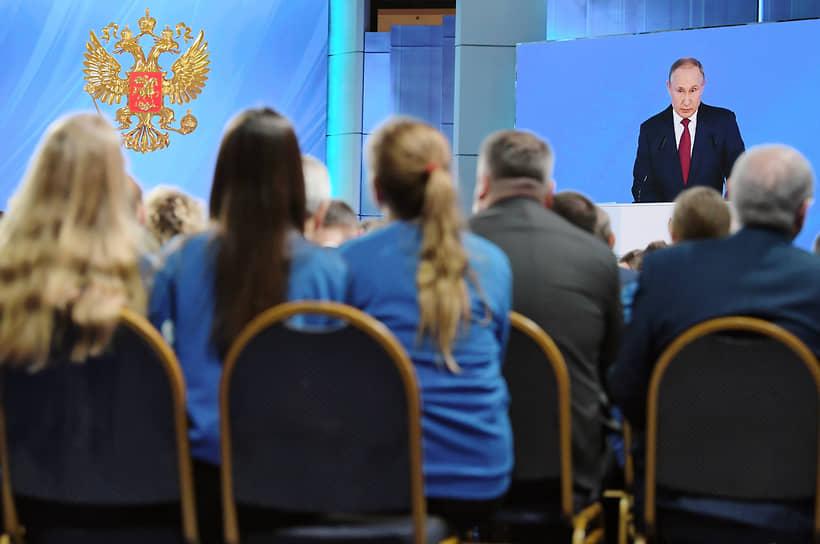 Президент России Владимир Путин (на экране) во время ежегодного Послания Федеральному Собранию