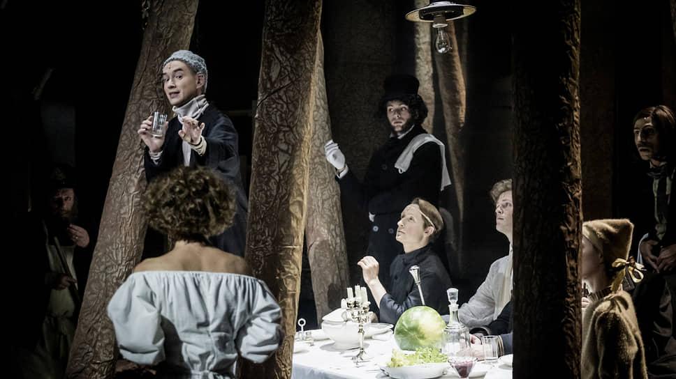Постановщик сводит обэриутов и их героев за пиршественным столом в потусторонне-мрачном лесу