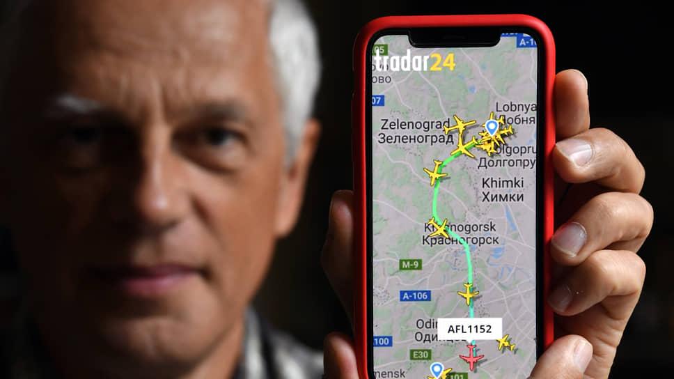 Схема полетов самолетов на экране смартфона в руке у жителя деревни Юрлово Олега Горошко