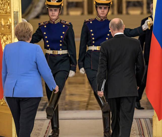 Ангела Меркель уходит, прощаясь. С Владимиром Путиным