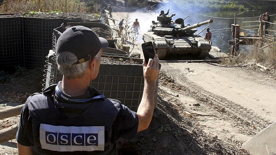 Европейцы из миссии ОБСЕ находятся на обеих сторонах конфликта в Донбассе. На фото: наблюдатель ОБСЕ фиксирует ввод украинских танков