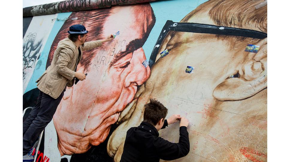 Дмитрий Врубель (слева) с сыном Артемом реставрируют знаменитую картину на остатке Берлинской стены
