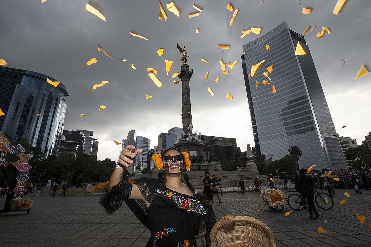 Женщина бросает бумажные цветы в воздух, на параде в День мертвых на проспекте Реформы в Мехико
