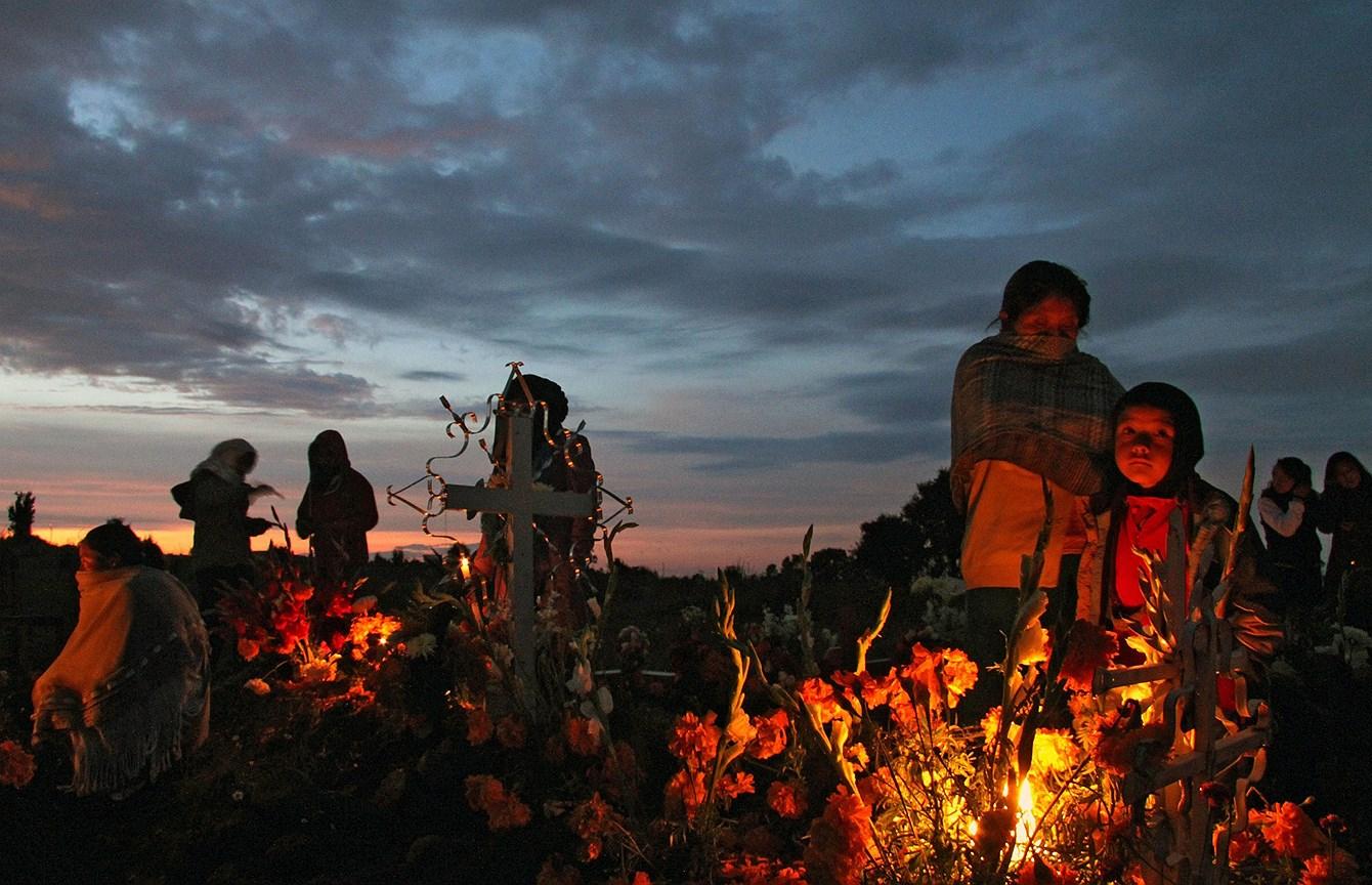 Люди украшают могилу родственника на кладбище в Сан Исидро Буэнсусесо, штат Тласкала, Мексика