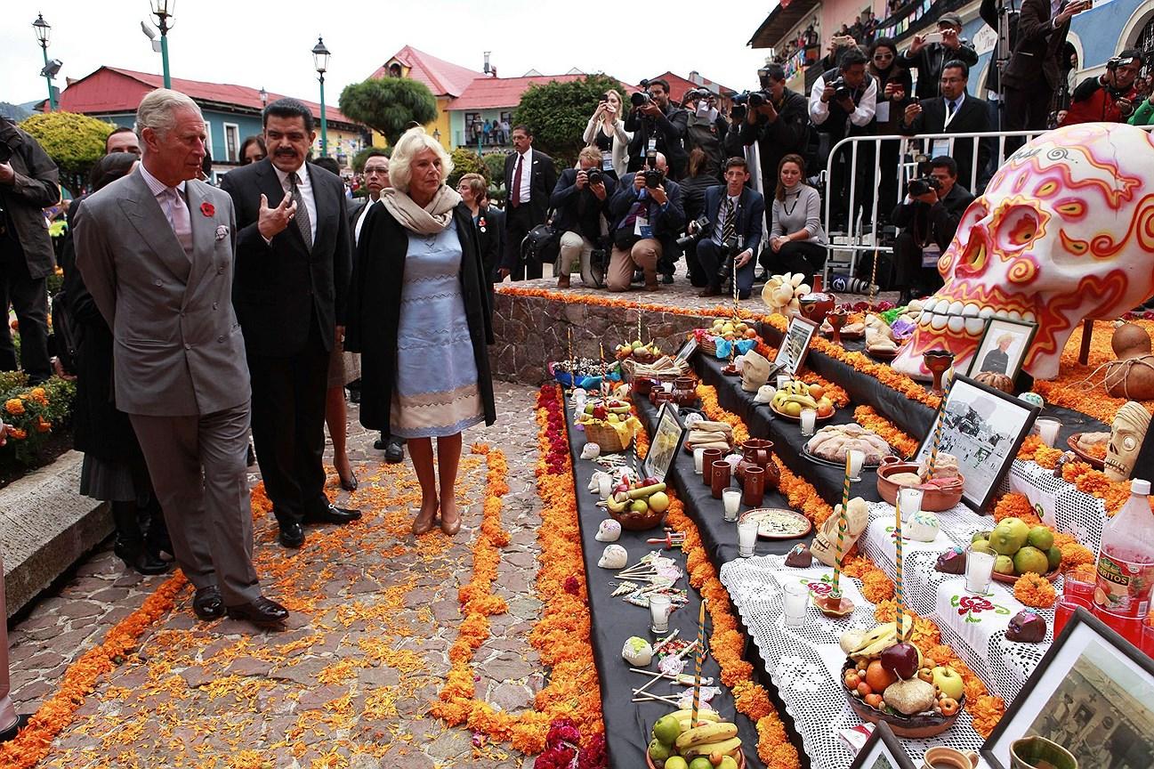 Принц Чарльз Уэльский (слева) и его жена Камилла герцогиня Корнуоллская (справа) посещают алтарь в День мертвых в городе Пачука в штате Идальго, Мексика, во время официального визита