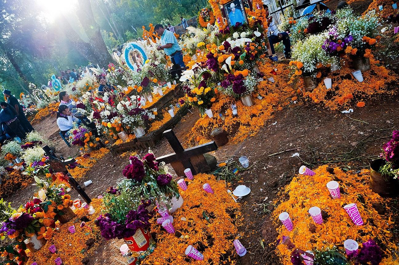 Мексиканские семьи собираются на кладбище, принося цветы и еду, чтобы почтить память  умерших родственников во время празднования Дня мертвых в Цурумутаро, Мичоакан, Мексика