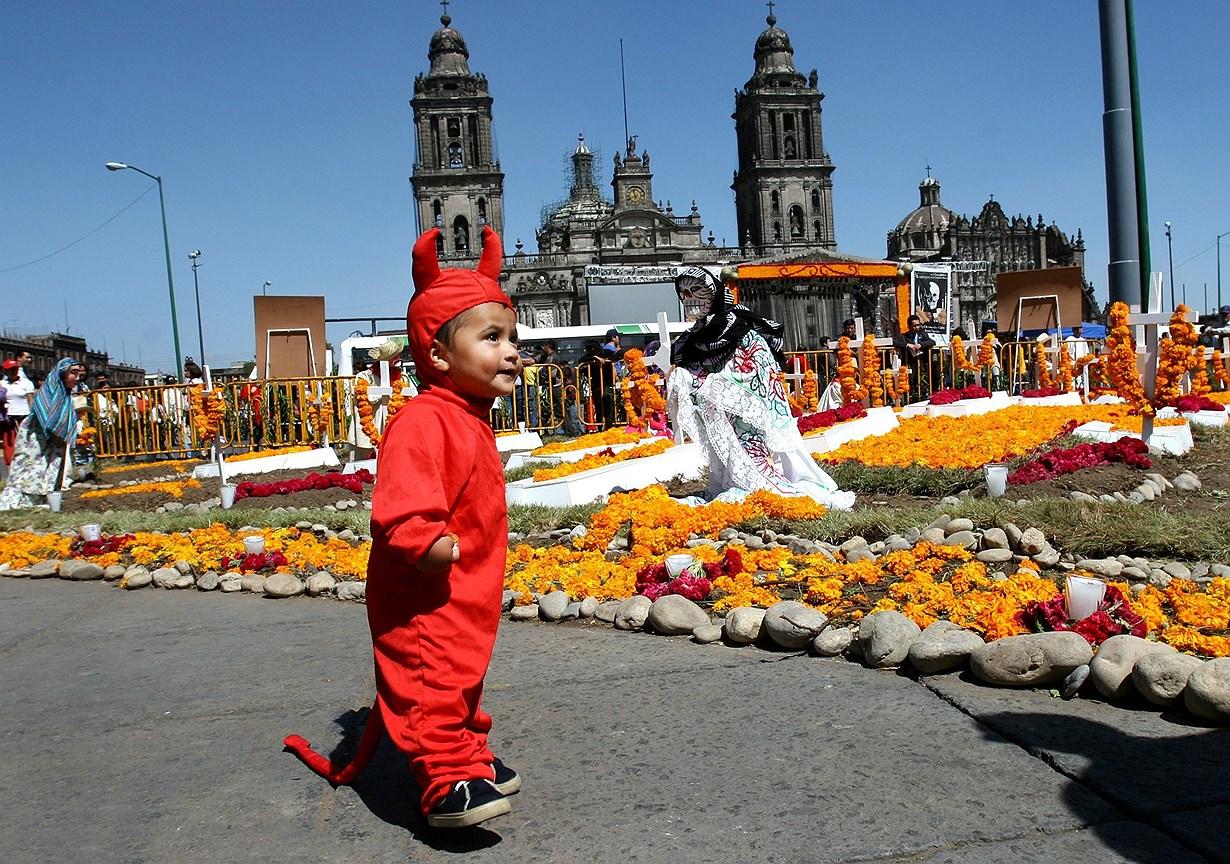 Мальчик в костюме чертенка на площади Cокало во время празднования Дня мертвых в Мехико