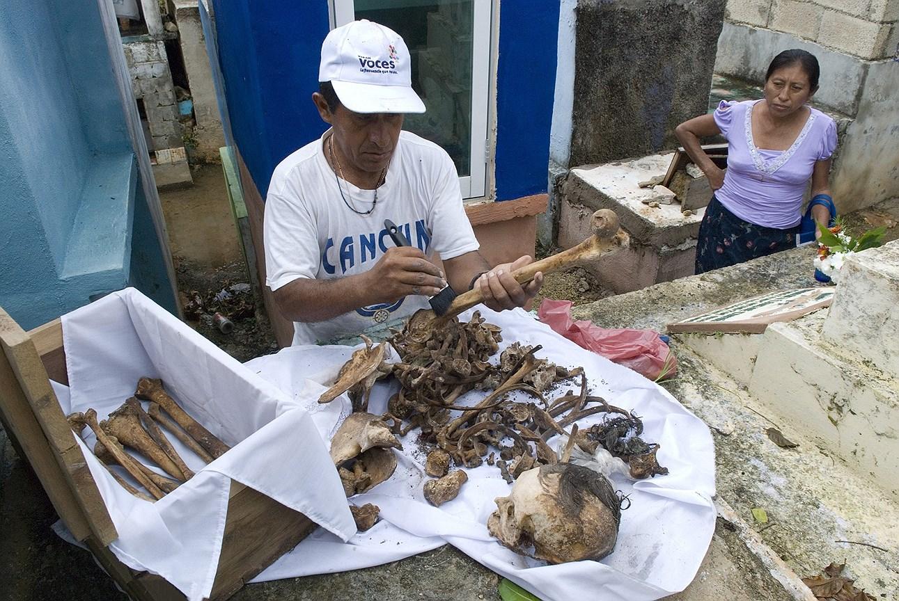 Житель поселка Помуч  очищает кости своих близких, чтобы разместить их на обозрение среди цветов и новой ткани для почитания в День мертвых