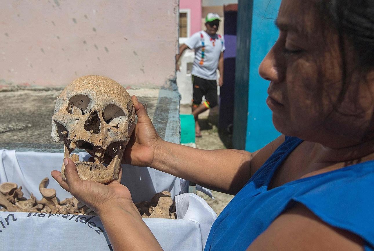 Женщина очищает кости любимого человека в День мертвых, в поселке Помуч, штат Кампече, Мексика