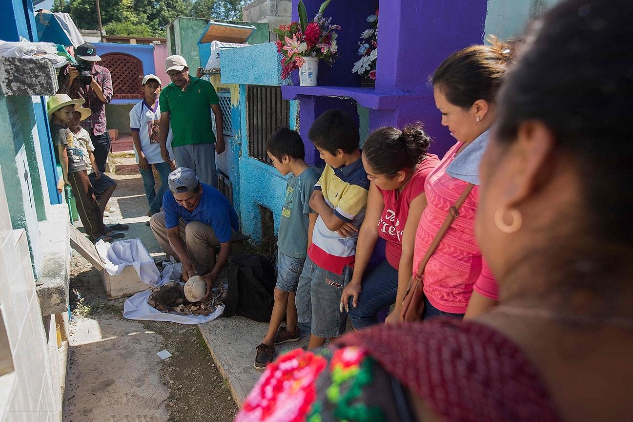 Семья усопшего на кладбище в День мертвых, в поселке Помуч, Мексика