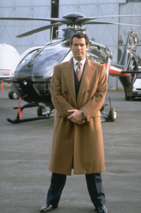 Воплощение строгого и сдержанного образа середины 1990-х: бежевое пальто (camel coat), костюм и изобретательный гаджет в руках<br> На фото: кадр из фильма «Завтра не умрет никогда», 1997 год