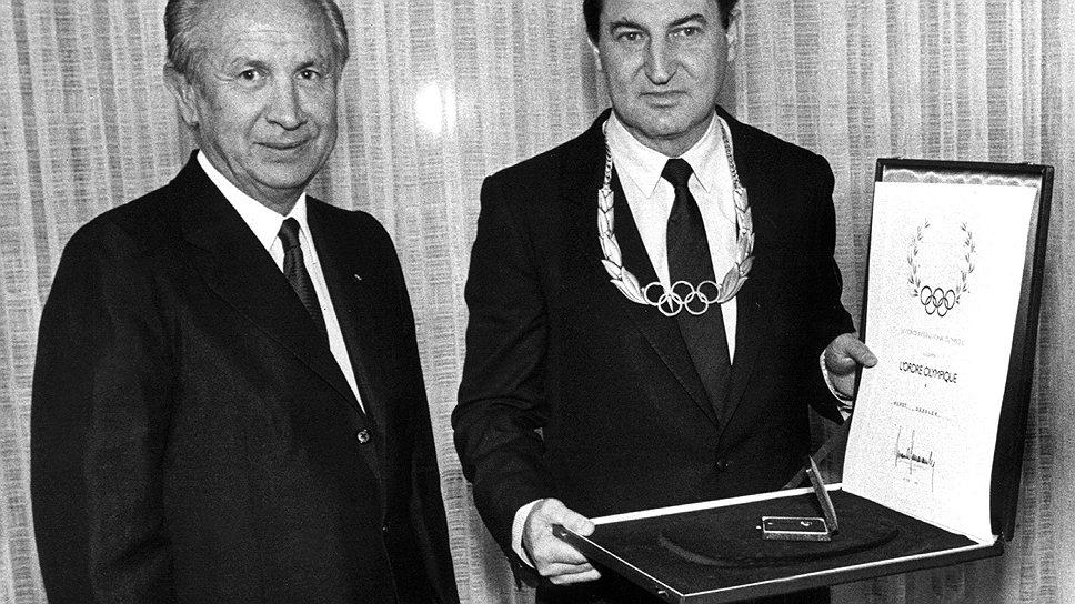 Глава Adidas Хорст Дасслер (справа) отдал МОК в руки Хуана Самаранча, чтобы украсить олимпийское движение тремя фирменными полосками