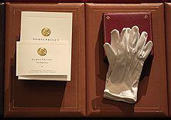 Нобелевскому лауреату вручается диплом (на фото слева), медаль (на снимке справа, в коробочке, под перчатками) и чек на 10 млн шведских крон (не представлен на фотографии)