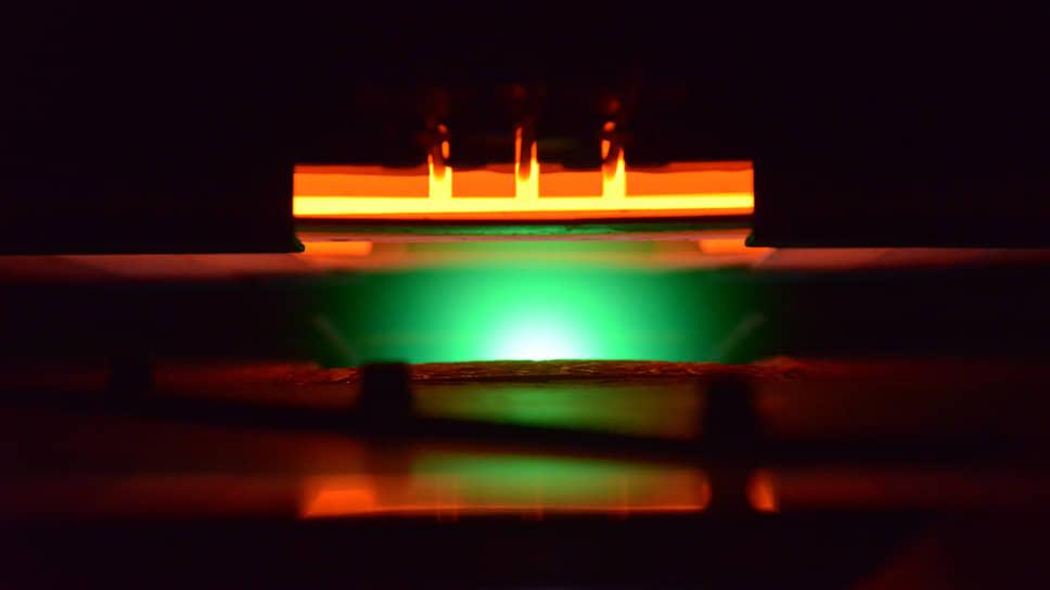 Процесс лазерного осаждения слоя сверхпроводника на металлическую ленту проходит в вакууме при температуре около 800 градусов