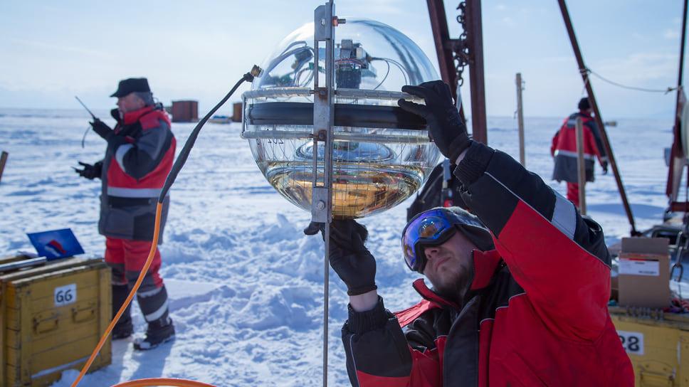 а фото участники байкальского эксперимента готовят к погружению под покрывающий озеро лед детектор черенковского излучения (оптический модуль). Фотоэлектронный умножитель и прочая электроника помещены внутрь выдерживающего давление полутора километров воды прозрачного шара. Это - часть телескопа, которая собирает и передает по кабелю на берег информацию о слабенькой вспышке, сопровождающей взаимодействие нейтрино в воде