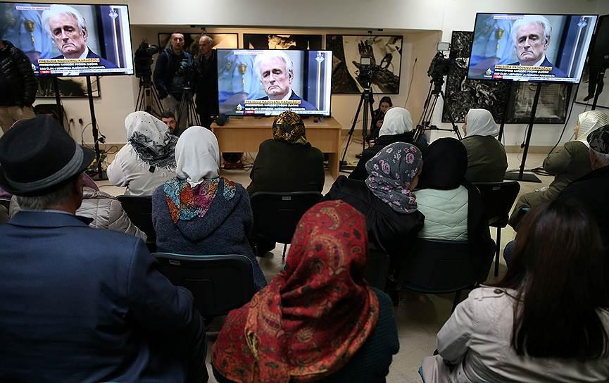 Люди в мемориальном центре около Сребреницы смотрят трансляцию суда над Радованом Караджичем