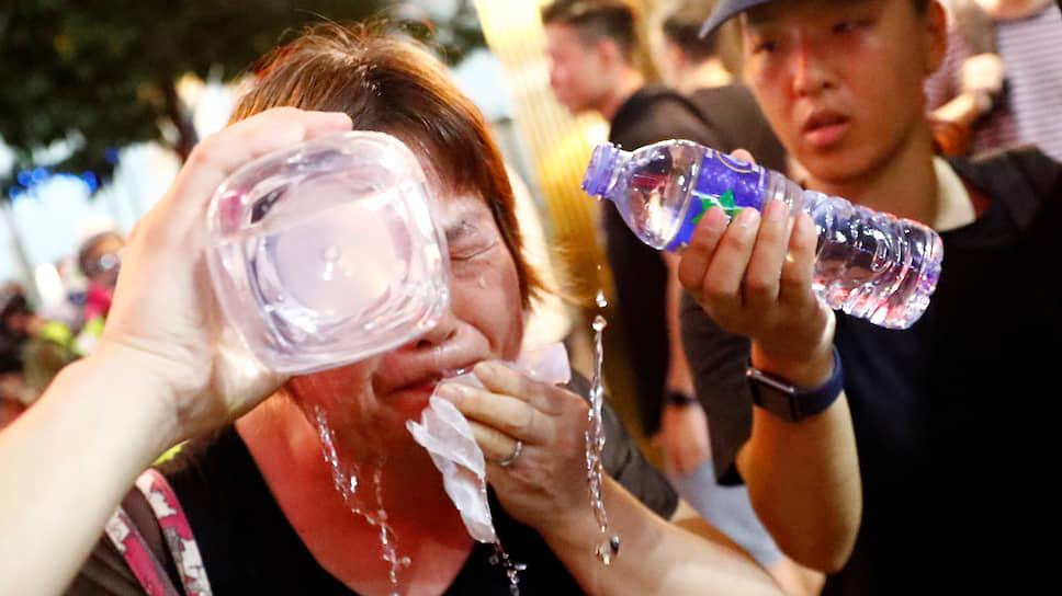 Женщина промывает глаза после применения полицией Гонконга слезоточивого газа