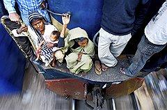 """Эта женщина с малышом заняла, пожалуй, одно из самых выгодных """"открытых мест"""" — в углу, да еще и рядом с поручнем. Неблизкий путь от Дакки до Силхета, 350 км, они проведут комфортно"""
