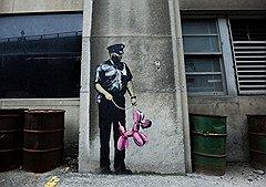 """Рисунки, сделанные Бэнкси на стенах в Торонто (полицейский с надувной собакой) и городе Парк Сити (США, Юта) во время международного кинофестиваля независимого кино """"Санденс"""""""