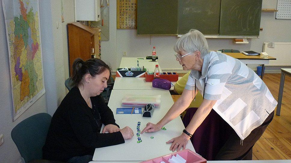 Учительница фрау Люттих объясняет одной из слушательниц курсов разницу между гласными и согласными звуками