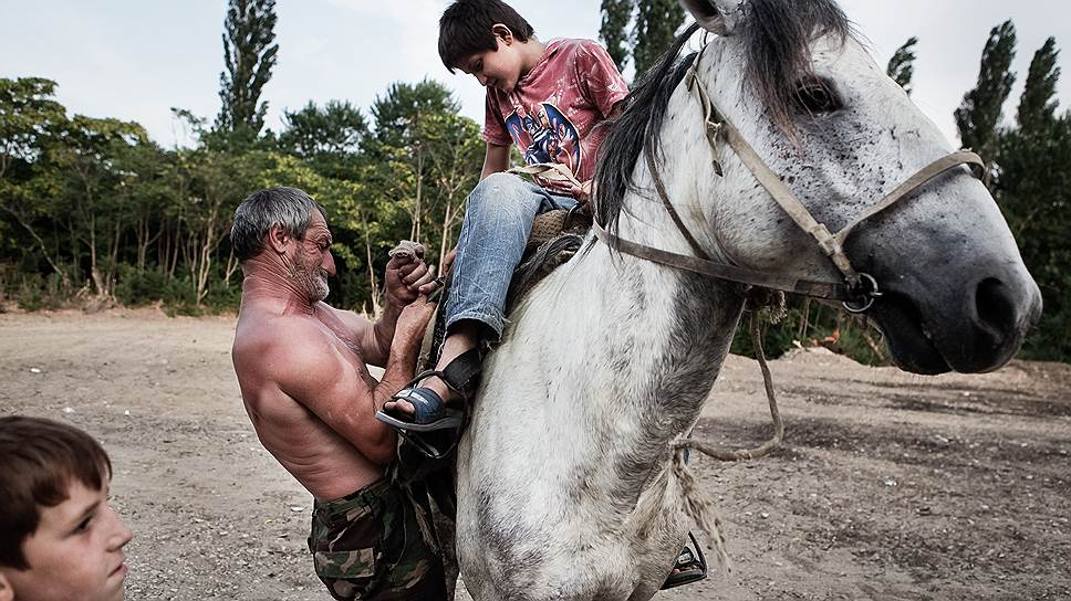 Братья седлают коня в Сарыкуме, одном из самых жарких мест в Дагестане