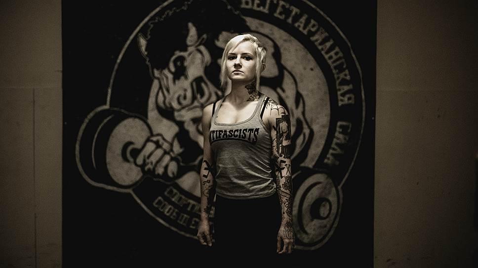 """Оксана (25 лет) в тренажерном зале """"Вегетарианская сила"""". Оксана занимается пауэрлифтингом, следует принципам веганства и стрейтэджа (против алкоголя, наркотиков и случайных половых связей), что обозначают татуировки-кресты на внутренней стороне локтей. Как и большинство панков, Оксана поддерживает антифашистское движение, которое ведет активную борьбу с неонацистскими группировками"""