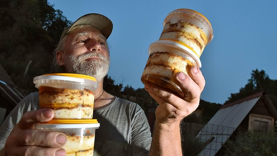 Юрий Карамзин кладет сыр в банки с оливковым маслом
