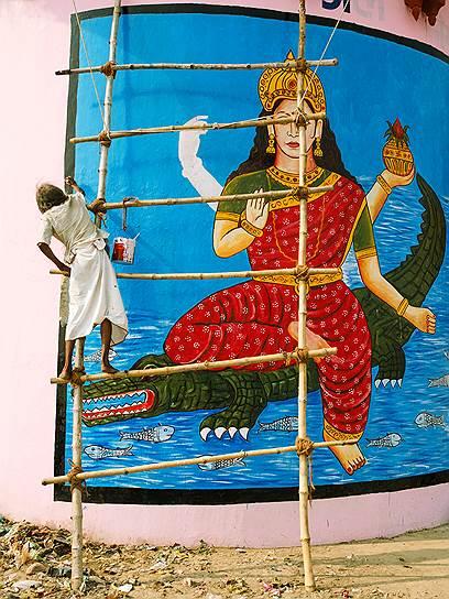 Местный художник рисует на стене изображение индийского божества