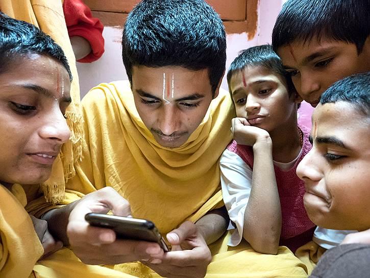 Студенты изучают содержимое айфона, но в большинстве случаев они пренебрегают мирскими благами