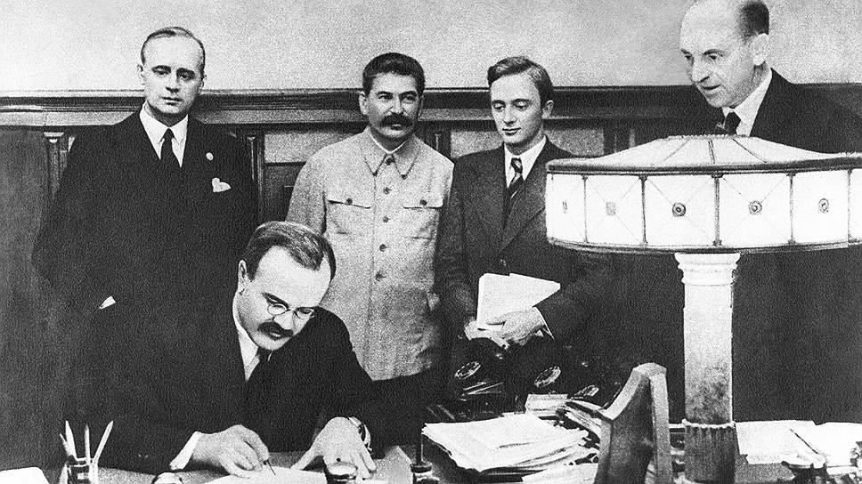 В.М. Молотов подписывает германо-советский договор о ненападении. Стоят (слева направо): Иоахим фон Риббентроп, И.В.Сталин, В.Н.Павлов, Ф.Гаус. 23августа 1939года