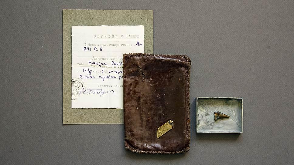 Справка о ранении от 14 сентября 1942 года. То самое кожаное портмоне с памятной гравировкой, пробитое осколком снаряда. Рядом часть второго осколка разорвавшегося снаряда, который попал в ногу