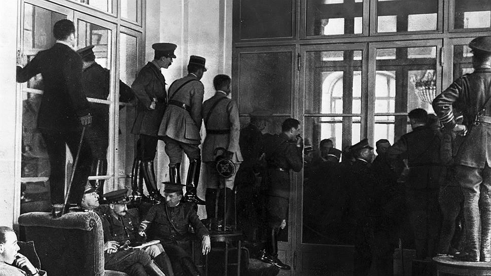 Офицеры союзников стоят на стульях и столах, чтобы заглянуть в Зеркальный зал, где подписывается Версальский мирный договор