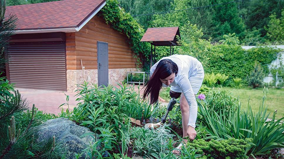 Женщина любит ухаживать за растениями на приусадебном участке