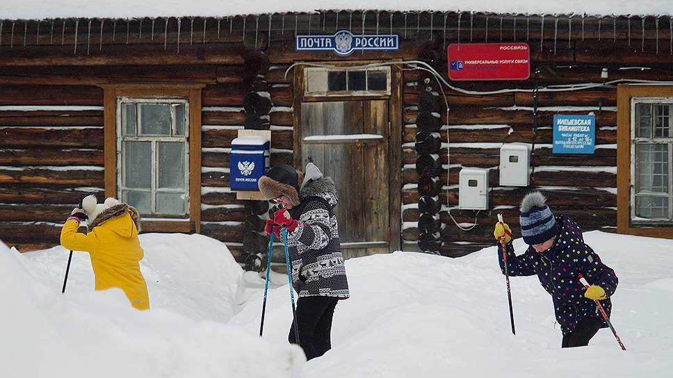 Во время урока физкультуры дети катаются на лыжах по деревне