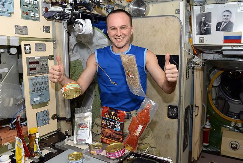 Космонавт Сергей Рязанский с традиционной космической едой: здесь и закуски, и суп, и второе блюдо, и даже компот с десертом