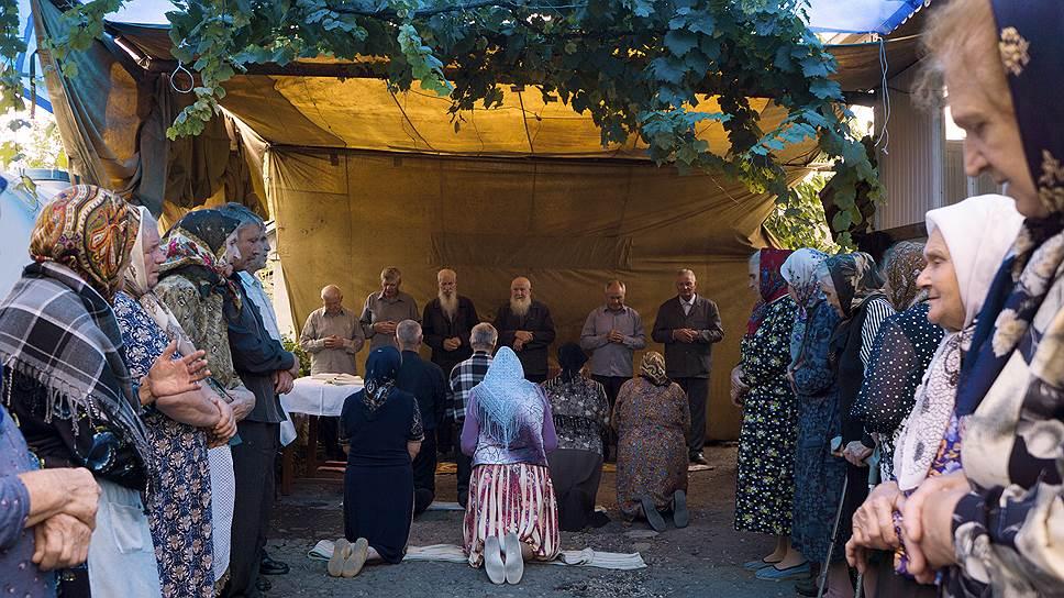 Обряд прощания с умершим у молокан. На сороковой день после смерти члены семьи на коленях просят прощения у общины за себя и за покойного
