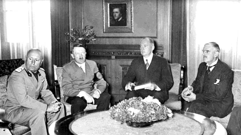 Это фото сделано в 1938 году в кулуарах Мюнхенской встречи. Слева направо: Муссолини, Гитлер, Пауль(Отто) Шмидт (официальный переводчик фюрера с 1935 г., штандартенфюрер с 1940 г.), британский премьер Чемберлен