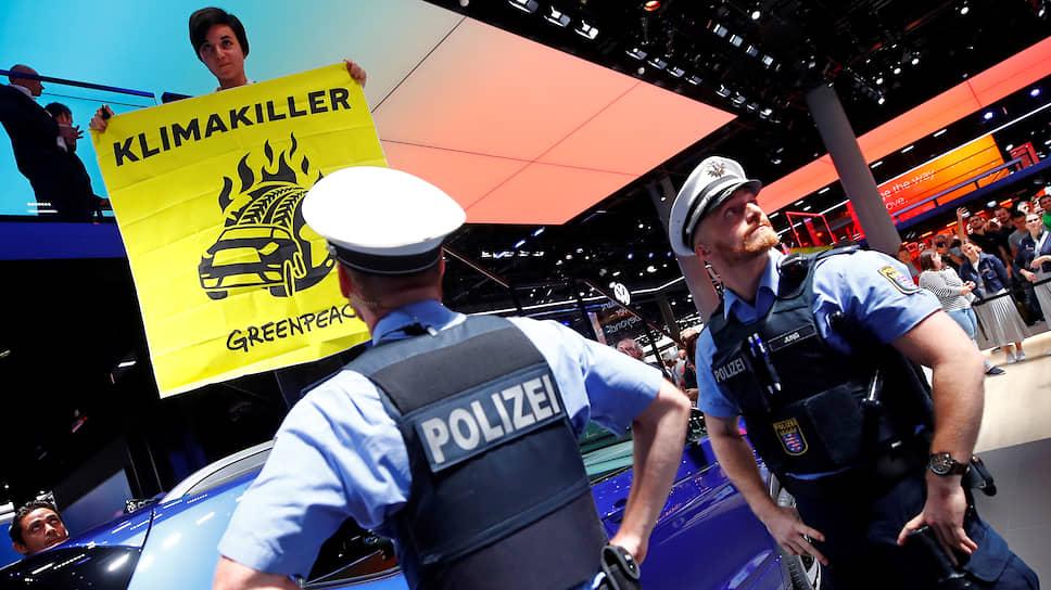 Офицеры полиции приглядывают за активистом «Гринпис», который разворачивает плакат про то, что автомобили — «убийцы климата»