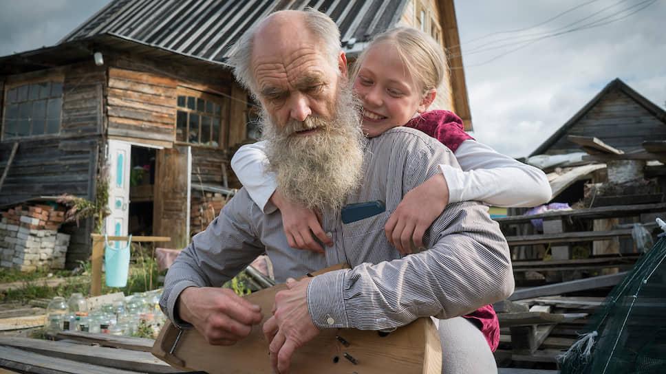 Александр Келарев играет на гуслях с дочерью Катериной возле их дома в селе Пежма