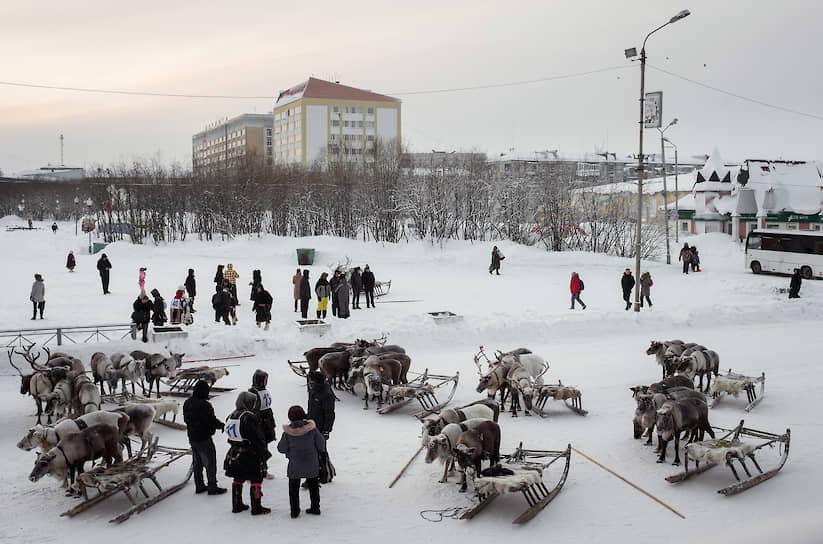 Оленеводы в ожидании гонки на оленьих упряжках во время празднования Дня города