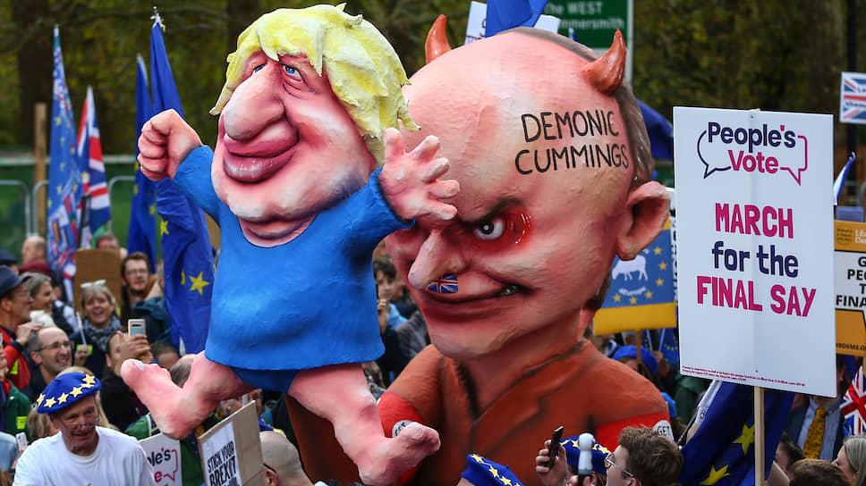 На недавнюю демонстрацию против предлагаемого правительством плана «Брексита» в Лондоне вышел миллион человек. Главу правительства оппоненты представили марионеткой, а демон за ним — его старший советник Доминик Каммингс, которого называют серым кардиналом