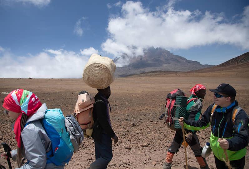 Носильщики, гиды, помощники гидов, даже повара сопровождают всех туристов, совершающих подъем на высочайший стратовулкан Африки