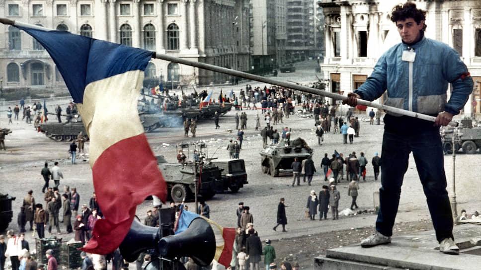 Утро после революции: молодой человек с флагом Румынии на балконе здания, где был ЦК компартии. Впереди — будни